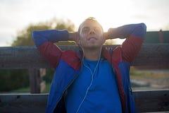Утомленное усаживание бегуна, ослабляя и слушая к музыке ваш телефон, глаза закрыло на деревянной пристани, спорте Стоковые Фото