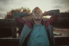 Утомленное усаживание бегуна, ослабляя и слушая к телефону музыки, глазам закрыло на деревянной пристани, спорте Стоковое Фото