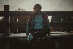Утомленное усаживание бегуна, ослабляя и слушая к телефону на деревянной пристани, спорту музыки Стоковые Изображения RF