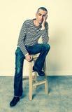 Утомленное усаживание молодого человека, сторона склонности в наличии к ворсине Стоковая Фотография RF