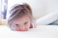 Утомленное ` t doesn дочери девушки хочет проспать вверх по смотреть камеру на родительской кровати ` s на утре Счастливая рассла Стоковые Фото