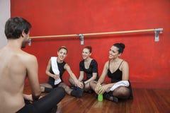 Утомленные артисти балета смотря тренера в студии стоковое фото