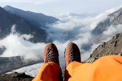 Утомленные ноги альпиниста в ботинках на горах Стоковые Изображения RF