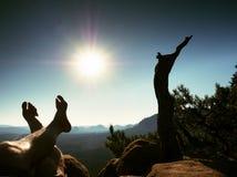 Утомленные потные ноги на пике утеса на сломленной сосне Горячий windless летний день Стоковые Фотографии RF