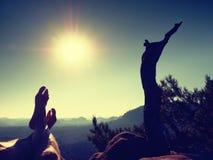 Утомленные потные ноги на пике утеса на сломленной сосне Горячий windless летний день Стоковые Изображения
