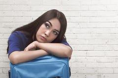 Утомленный азиатский путешественник женщины лежа вниз на голубом чемодане Стоковое Изображение RF