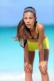 Утомленный бегун женщины после разминки дышая принимающ пролом от бежать на пляже Стоковая Фотография RF