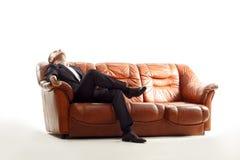 Утомленный бизнесмен при телефон сидя на софе Стоковые Фото