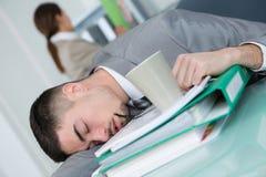 Утомленный бизнесмен спать на столе офиса Стоковое Фото