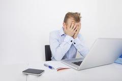 Утомленный бизнесмен с руками на стороне сидя на столе компьтер-книжкой Стоковая Фотография RF