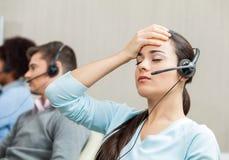 Утомленный женский агент обслуживания клиента в центре телефонного обслуживания Стоковые Фотографии RF
