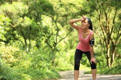 Утомленный женский бегун принимая остатки после бежать Стоковое фото RF
