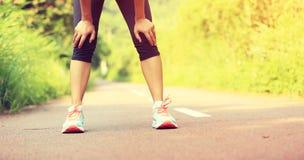 Утомленный женский бегун принимая остатки после бежать Стоковые Изображения