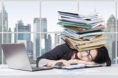 Утомленный женский работник с обработкой документов на голове Стоковые Фото
