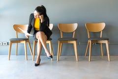 утомленный ждать Коммерсантка держа бумажной и смотря отсутствующий пока сидящ Стоковое Изображение RF