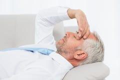 Утомленный зрелый бизнесмен отдыхая на софе в живущей комнате Стоковые Изображения RF