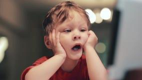 Утомленный милый мальчик в красной рубашке держит его руки около стороны, касающие щеки и имеет смешную смотря сторону видеоматериал