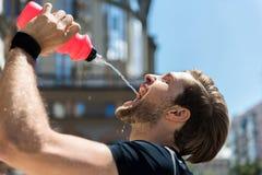 Утомленный моложавый бородатый спортсмен освежая пока тренирующ снаружи стоковое изображение rf