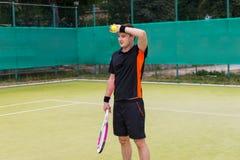 Утомленный молодой мужской теннисист после спички стоковое изображение rf