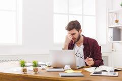 Утомленный, перегружающ бизнесмена с компьтер-книжкой в современном белом офисе Стоковое Изображение RF