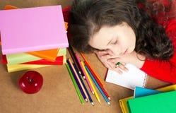 Утомленный сон усаживания девушки на таблице Стоковая Фотография RF