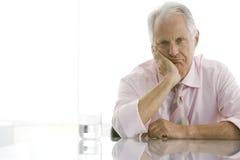 Утомленный старший бизнесмен сидя на столе Стоковое Изображение