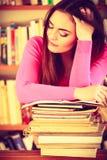 Утомленный студент девушки в библиотеке колледжа Стоковые Изображения RF
