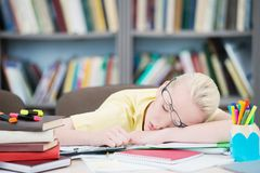 Утомленный студент с стеклами спать в библиотеке стоковая фотография