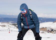 Утомленный человек вымотанный после достижения пикового саммита trekking в ландшафте зимы горы снега стоковые фотографии rf