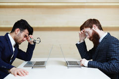2 утомленных бизнесмена работая в офисе Стоковая Фотография