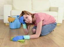 Утомлянная женщина усиленная и убирающ дом моя пол на ее коленях Стоковое фото RF