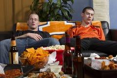 2 утомляли людей после смотреть игру спорт на ТВ, горизонтальном Стоковые Фото