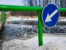 Утончите лед в реке около моста с предупредительным знаком Стоковые Изображения RF