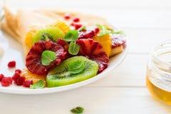Утончите crepes с свежим кивиом, апельсином, сицилийскими листьями апельсина, меда, сливк и мяты Стоковые Фотографии RF