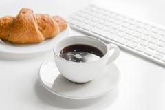 Утро бизнесмена с клавиатурой, чашкой кофе и круассаном на белой предпосылке таблицы Стоковое Изображение