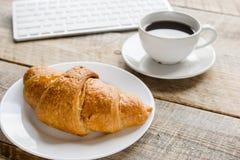 Утро бизнесмена с клавиатурой, чашкой кофе и круассаном на предпосылке деревянного стола Стоковая Фотография