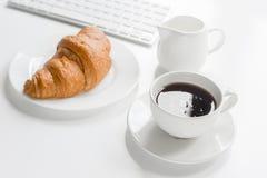 Утро бизнесмена с клавиатурой, чашкой кофе и croussant на белой предпосылке таблицы Стоковая Фотография