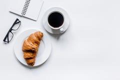 Утро бизнесмена с тетрадью, чашкой кофе и круассаном на модель-макете взгляд сверху предпосылки деревянного стола Стоковая Фотография