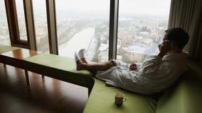 Утро в роскошной гостинице Вид сзади красивого молодого бизнесмена звоня, сидя на софе около панорамного окна видеоматериал