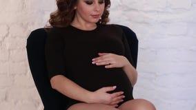 Утро молодой беременной женщины одетое в черном bodysuit будущая счастливая мать сток-видео