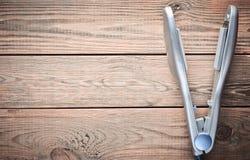 Утюг для выравнивать волосы на деревянном столе близкие раскручиватели съемки волос вверх скопируйте космос Взгляд сверху стоковое фото rf