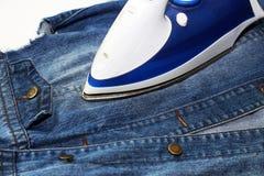Утюг и джинсовая ткань, забота одежд Стоковое фото RF