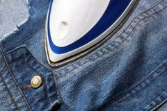 Утюг и джинсовая ткань, забота одежд Стоковое Изображение