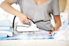 Утюг одежд женщины утюжа в прачечной Стоковые Фото