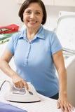 утюживя женщина рубашки Стоковая Фотография