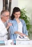 утюживя следующий старший к детенышам женщины Стоковые Изображения RF