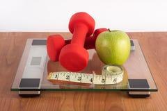 Утяжелите масштаб с красной гантелью, измеряя лентой и свежим зеленым яблоком на деревянном поле стоковая фотография