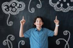 Ухищренный мальчик смотря вверх и указывая его пальцы вверх Стоковая Фотография RF