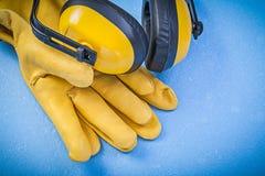 Ухо уменьшения шума muffs кожаные защитные перчатки на задней части сини Стоковые Изображения RF