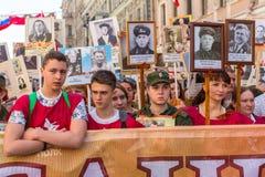 Участники бессмертного полка - общественного действия, во время которого участники снесли знамена/портреты стоковые изображения rf